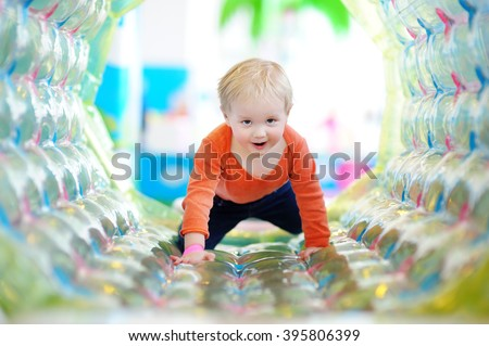 Active toddler boy playing at indoors playground