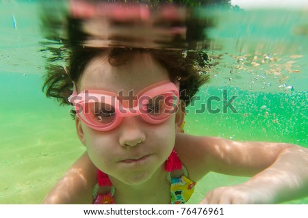 Active underwater kid in sea. Girl swims and having fun. Child sport on summer vacation - stock photo