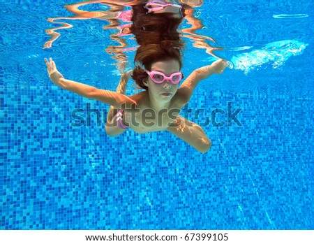 Active underwater kid in swimming pool. Girl swims and having fun. Child sport on summer vacation - stock photo