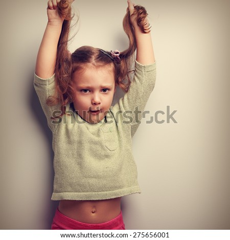 Active unhappy emotion kid girl pulling her long hair up. Vintage closeup portrait - stock photo