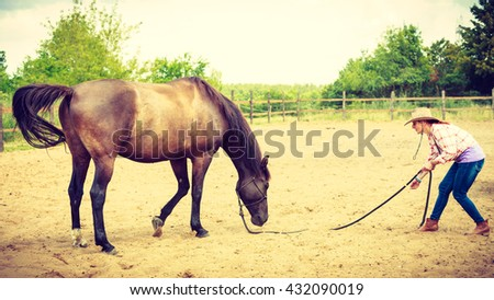 Active western cowgirl woman in hat with horse. American girl in countryside ranch. - stock photo