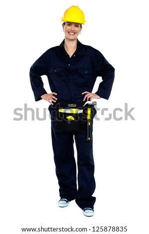 Active woman construction worker in overalls posing with hands on waist. - stock photo