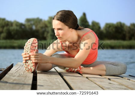 Active woman doing stretching exercise outdoors - stock photo