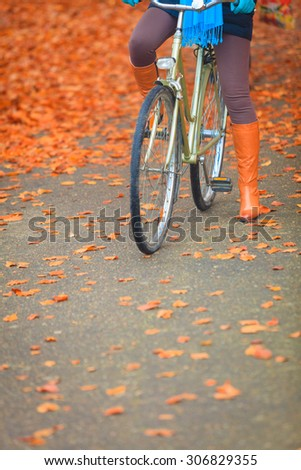 Active woman girl riding bike bicycle relaxing in fall autumn park. Healthy lifestyle and recreation leisure activity. - stock photo