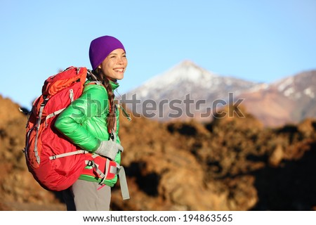 Active woman hiker living healthy lifestyle hiking outdoors wearing backpack smiling happy. Beautiful female trekking with looking with aspirations on Teide, Tenerife, Canary Islands, Spain, - stock photo