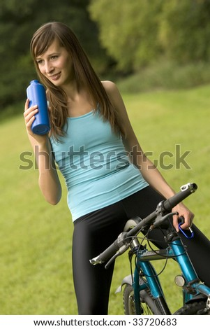 active woman on a bike drinking water