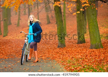 Active woman riding bike bicycle in fall autumn park. Young girl in jacket and scarf relaxing. Healthy lifestyle and recreation leisure activity.