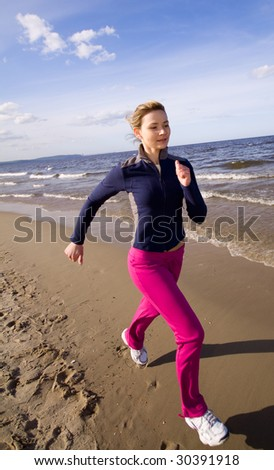 Active woman running on the beach - stock photo