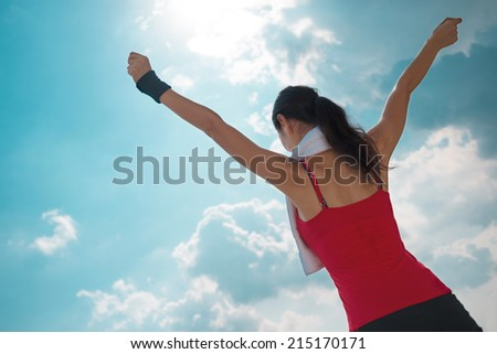 Active woman with outstretched arms against the blue sky, rear view - stock photo