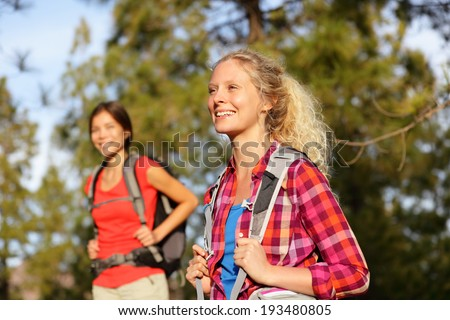 Active women - hiking girls walking in forest living healthy lifestyle doing outdoor activities. Female hikers trekking outside in woods wearing backpacks. Portrait of beautiful young blond hiker. - stock photo