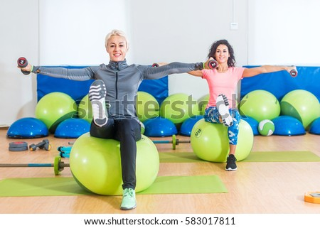 Active women sitting on exercise balls lifting legs and doing dumbbell lateral raise. Two mature females working out in a gym.