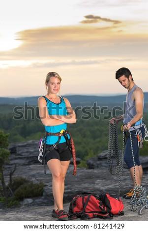 Active young couple rock climbing reach top at sunset - stock photo
