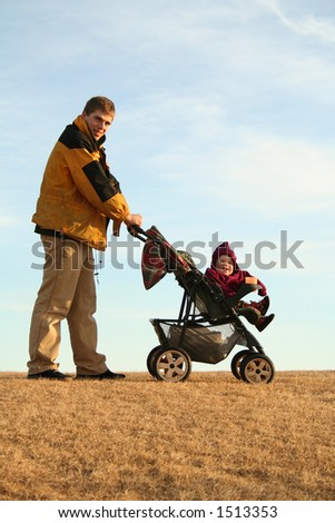 active young dad with his child in a stroller happy to take a walk in the park on a sunny day, against blue sky - stock photo