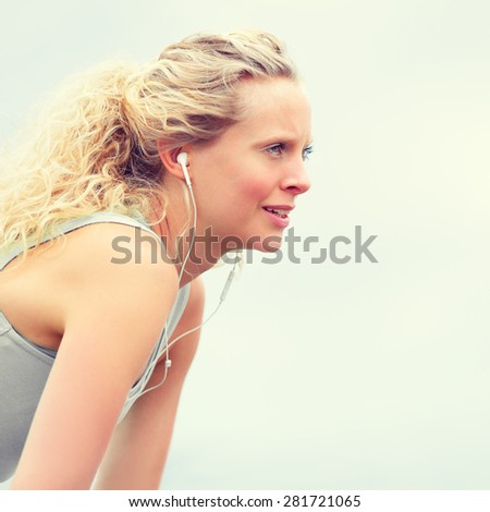 Active young fit woman exercising with earphones. Young fitness woman taking a break outside in summer fitness workout. Beautiful caucasian female model in running lifestyle listening to music. - stock photo