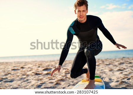 Active Young Male Surfer in Wetsuit, Demonstrating Proper Balance in Standing Position on Surfboard at the Beach Sand While Looking at the Camera.