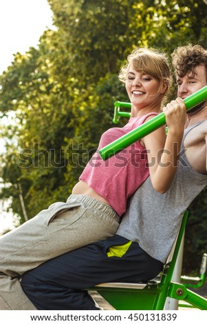 Active young man and woman exercising on pulldown machine. Muscular strong guy and girl in training suit working out at outdoor gym. Sport fitness and healthy lifestyle concept. - stock photo