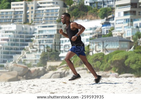 Active young man exercise running on the beach - stock photo