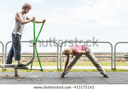 Active young man exercising on elliptical trainer machine and woman stretching. Muscular sporty guy and girl in training suit working out at outdoor gym. Sport fitness and healthy lifestyle concept. - stock photo