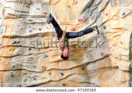 active young man on rock wall in sport center - stock photo