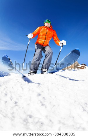 Active young man ready to skiing view from below during sunny winter day on Krasnaya polyana ski resort and Caucasus mountains in Sochi, Russia - stock photo