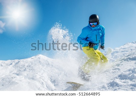 Active young man snowboarding from the hill at a winter ski resort