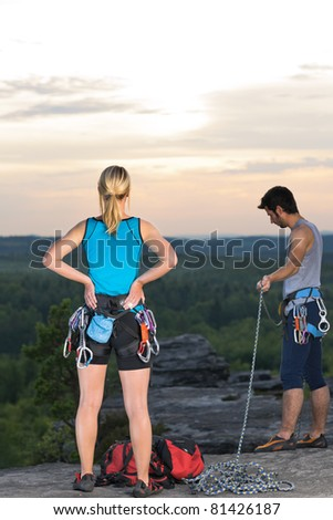 Active young people rock climbing reach top at sunset - stock photo