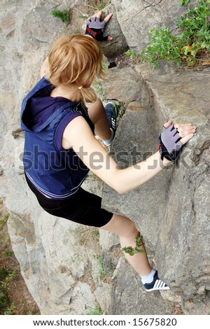 Active young woman climbing up the rock - stock photo