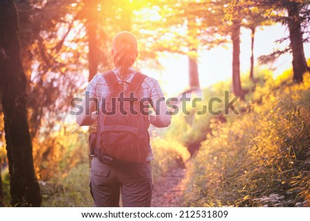 Active young woman hikes on a forest trail at sunset with a backpack on her back. Photographed in summer. - stock photo