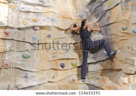active young woman on rock wall in sport center - stock photo