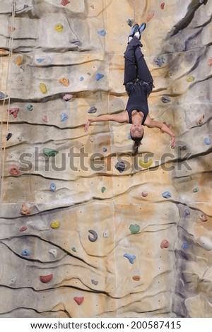 active young woman on rock wall in sport centre - stock photo