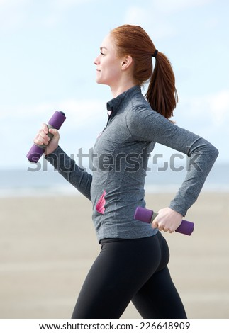 Active young woman walking with weights outdoors - stock photo