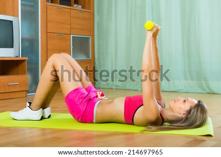 Active young woman working out with dumbbells at home - stock photo