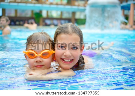 Activities on the pool. Cute kids - sister and brother swimming and playing in water in swimming pool in aquapark - stock photo