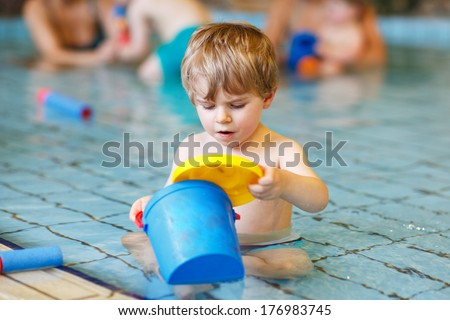 Activities on the pool, toddler boy swimming, having fun and playing in water, indoor - stock photo