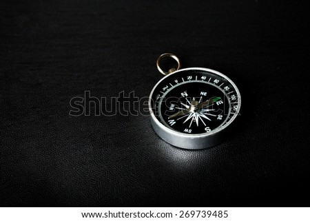 Activity. Compass on  black board background - stock photo