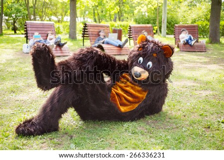 actor dressed as bear lies on grass in park and people on loungers with gadgets - stock photo