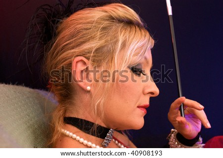 Actress dressed up as old fashioned madam or prostitute looking out of the corner of her eye at viewer.  Shot with blue and red strobes. - stock photo