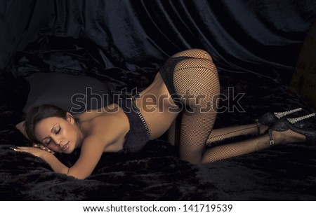 Actress model posing as sexy alluring woman in fishnet stockings - stock photo