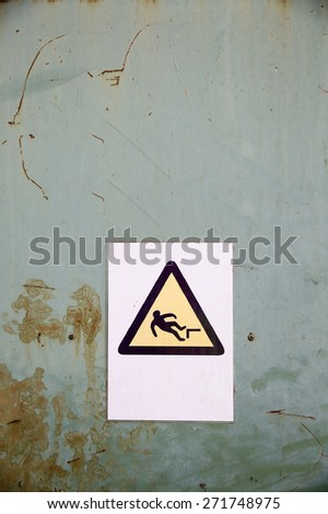Actual fall (trip) hazard sign, symbol warning workers and passers-by of danger and risk of falling, on uniform industrial rusty steel background. Safety and liability measures concept.  - stock photo