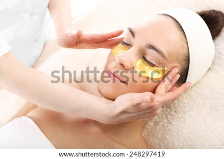 Acupressure, massage his temples, golden flakes collagen.Cosmetic procedure, the woman's face with gold flakes under the eyes and on the lips  - stock photo