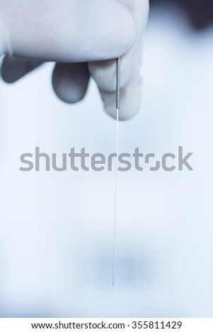 Acupuncture needle used for dry needling rehabilitation medical treament for physiotherapy and pain due to physical injury in the hand of the doctor. - stock photo
