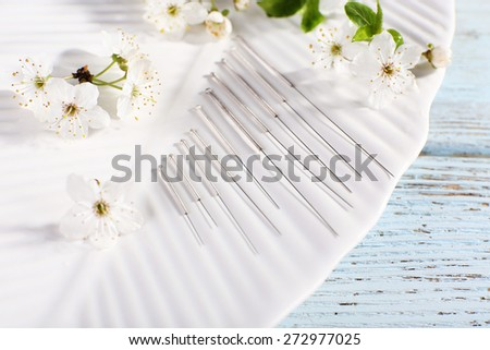Acupuncture needles and flowering branch on plate on wooden table, closeup - stock photo