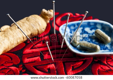 Acupuncture needles,ginseng root and herbal pills - stock photo