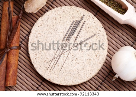 Acupuncture needles laying on the stone mat and herbs like garlic. TCM Traditional Chinese Medicine concept photo - stock photo