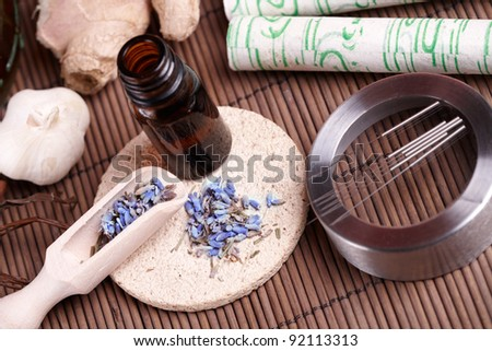 Acupuncture needles laying on the stone mat, moxa sticks on wooden desk and lavender petals with macerated oil. TCM Traditional Chinese Medicine concept photo - stock photo