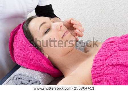Acupuncture needles on head of a young woman - stock photo