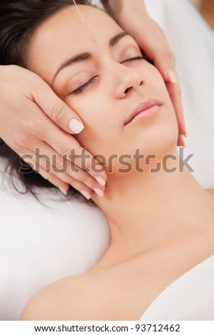 Acupuncture needles on head of a young woman at the spa - stock photo
