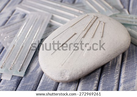 Acupuncture needles on wooden table with spa stones, closeup - stock photo