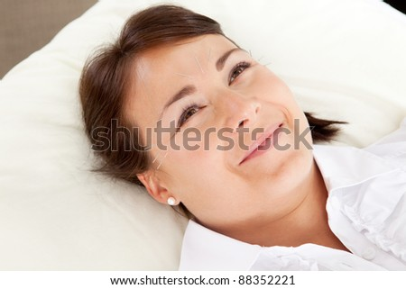 Acupuncture patient smiling and looking up - stock photo