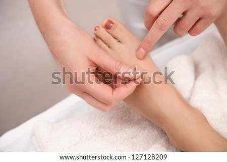 Acupuncture treatment on foot with red toenail - stock photo